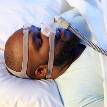 Man with Sleep Apnea Sleeping with a CPAP continuous positive airway pressure machine